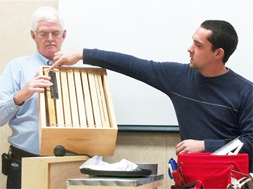 Trevor Qualls (on the right) during a beekeeping demonstration